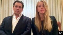 In this image made from video released by the Australian Government Department of Agriculture and Water Resources on Monday, April 18, 2016, actor Johnny Depp and his wife, Amber Heard speak in a videotaped apology played during Monday's hearing at the So