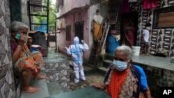 Seorang petugas kesehatan memanggil orang-orang untuk keluar untuk pemeriksaan gejala Covid-19 di Dharavi, salah satu daerah kumuh terbesar di Asia, di Mumbai, India, Selasa, 11 Agustus 2020. (Foto: AP)