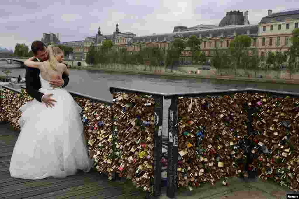 """Dominika dan Bartek Mieczkowski, pasangan yang baru menikah dari Polandia, berpelukan dekat pagar yang penuh dengan """"gembok cinta"""" di sebuah jalan menuju jembatan """"Pont des Arts"""" di atas Sungai Seine di Paris, Perancis."""