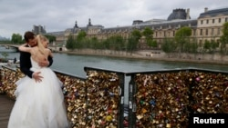 "A recently-married couple from Poland, Dominika and Bartek Mieczkowski, embrace near grills covered with ""love locks"" on a walkway which leads to the Pont de Arts over the River Seine in Paris, France, May 31, 2015."