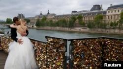 Pasangan yang baru menikah dari Polandia, Dominika dan Bartek Mieczkowski, berpelukan dekat pagar jembatan yang dipenuhi dengan gembok cinta di jembatan menuju Pont de Arts di sungai Seine di Paris, Perancis (31/5).
