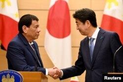 30일 일본을 방문한 로드리고 두테르테 필리핀 대통령(왼쪽)이 도쿄 총리 관저에서 아베 신조 일본 총리와 정상회담을 가진 후 공동기자회견에서 악수하고 있다.