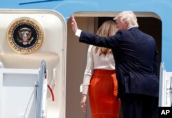 President Donald Trump, accompanied by first lady Melania Trump, waves as they board Air Force One at Andrews Air Force Base, Maryland, May 19, 2017, prior to his departure on his first overseas trip.