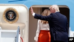 President Donald Trump, accompanied by first lady Melania Trump, waves as they board Air Force One at Andrews Air Force Base, Maryland, May 19, 2017, prior to his departure on his first overseas trip as president.