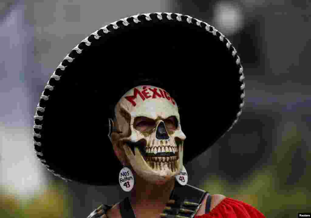 A demonstrator wearing a skull mask takes part in a protestin Mexico City to mark the eleven-month anniversary of their disappearance. The students' disappearance on the night of Sept. 26, 2014, in the southwestern city of Iguala triggered massive protests in Mexico and calls for justice.