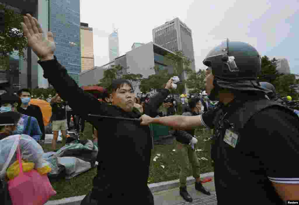 A pro-democracy protester blocks a riot policeman during a clash outside the government headquarters in Hong Kong, December 1, 2014.