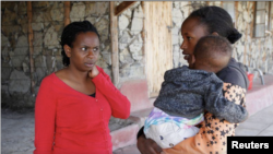 FILE - Serene Haven secondary school founder Elizabeth Wanjiru talks to Josephine Wanjiru, 19, who carries her child outside a dormitory at the Serene Haven secondary school, accommodating pregnant girls and teenage mothers with their babies in Nyeri, Kenya January 20, 2021.