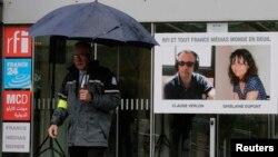 Hình phóng viên Ghislaine Dupont (phải), 51 tuổi, và kỹ thuật viên radio claude Verlon, 58 tuổi, bị giết tuần trước ở Mali, được treo tại cổng vào toà nhà đài RFI ở Issy-les-Moulineaux gần Paris, 5/11/2013.