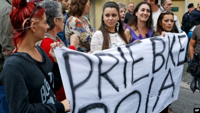 "Demonstrators hold up a sheet with writing reading in Italian ""Priebke murderer"" outside the Society of St. Pius X, a schismatic Catholic group, where Nazi war criminal Erich Priebke funeral was taking place, in Albano Laziale, on the outskirts of Rome, O"