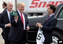 FILE - Wisconsin Gov. Scott Walker, right, presents President Donald Trump with a Milwaukee Buck basketball hat and jersey as he arrives in Kenosha, Wisconsin, April 18, 2017.