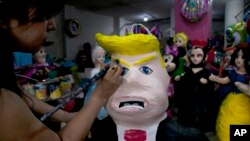 """FILE - Alicia Lopez Fernandez paints a pinata depicting Donald Trump at her family's store """"Pinatas Mena Banbolinos"""" in Mexico City, July 10, 2015. In a surprise move, Donald Trump will travel to Mexico Aug. 31 to meet with President Enrique Pena Nieto."""