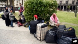 A group of Syrian refugees gather with their belongings in Independence Square in Montevideo, Uruguay, Sept. 7, 2015.
