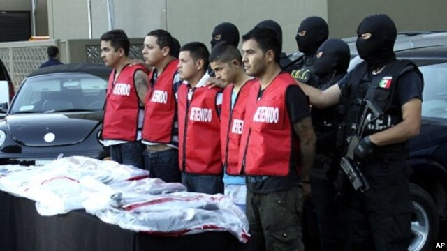 State investigation agents escort the five arrested men in connection with an attack at the casino last week that killed 52 people, during a presentation in Monterrey, August 30, 2011