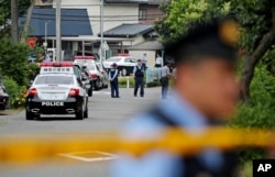 Police officers stand guard at a crossroad near the Tsukui Yamayuri-en, a facility for the handicapped, where a number of people were killed and dozens injured in a knife attack in Sagamihara, outside of Tokyo, Japan, July 26, 2016.