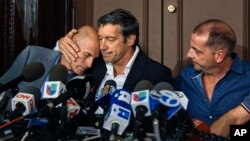 Survivors of the attack Guillermo Banchini, center, hugs Ivan Brajkovic, left, next to Juan Pablo Trevisan, during a press conference, Nov. 3, 2017, in New York.