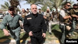 FILE - Iraq's Prime Minister Haider al-Abadi (in black) walks during a visit to an Iraqi army base in Camp Tariq near Fallujah, Iraq, June 1, 2016. Abadi is calling on residents of Mosul to cooperate with government forces that will be participating in operations to retake the city from IS militants.