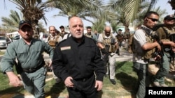 FILE - Iraq's Prime Minister Haider al-Abadi (front 2nd L) walks during his visit to an Iraqi army base in Camp Tariq near Fallujah, Iraq, June 1, 2016.