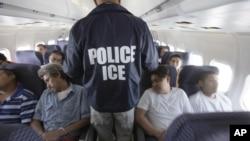 Petugas Imigrasi berjalan di dalam pesawat charter yang penuh dengan imigran yang akan dideportasi, dalam penerbangan dari Chicago ke Texas (Foto: dok/ AP Photo/LM Otero).