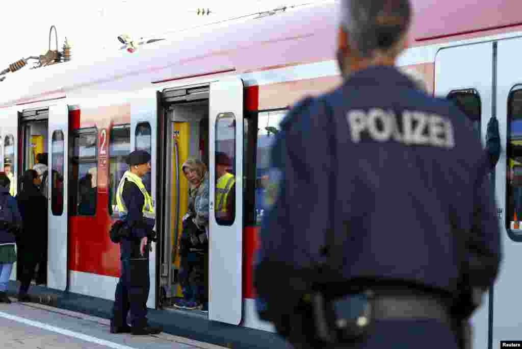 Migrants enter a regional train at the main railway station in Munich.