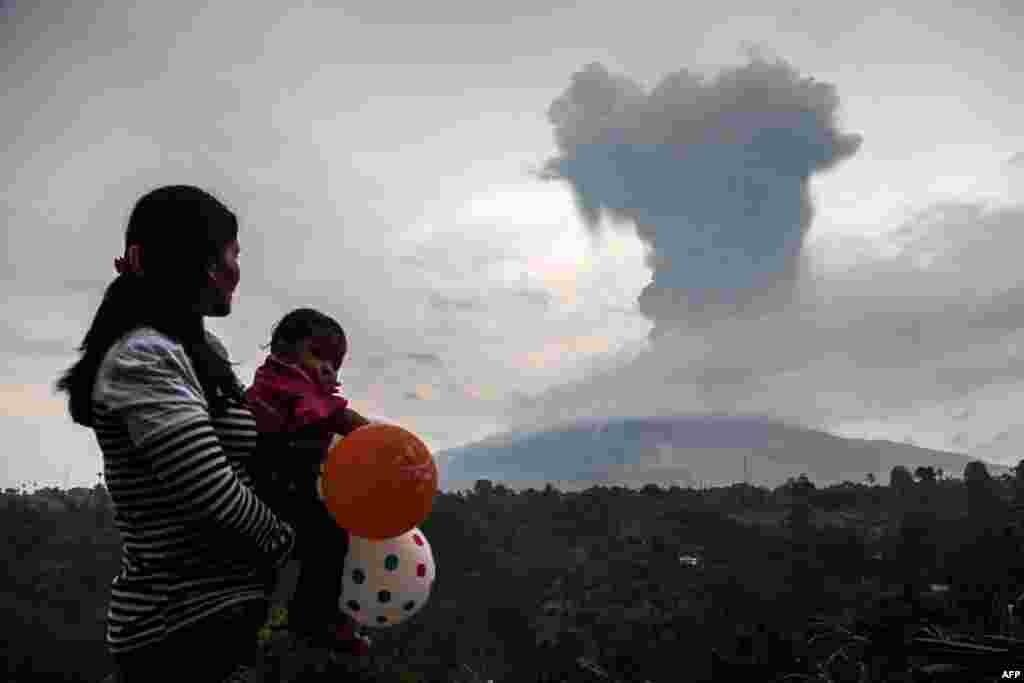 زن اهل اندونزی به همراه فرزندش به خاکستر و دود ناشی از فوران کوه آتشفشان در آن کشور نگاه می کند.