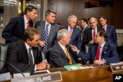 FILE - Members of the Senate committee speak together before Secretary of State John Kerry, Secretary of Energy Ernest Moniz and Secretary of Treasury Jack Lew arrive to testify at a Senate Foreign Relations Committee hearing on Capitol Hill, in Washington, July