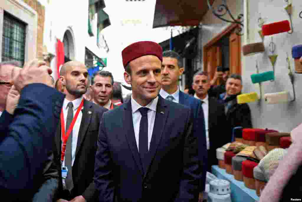 French President Emmanuel Macron wears a fez during his tour of the Medina (old town) of the Tunisian capital Tunis.