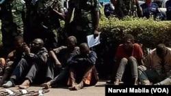 Des présumés bandits armés assis à même le sol, mains liées, entourés des forces de sécurité lors de leur présentation au public à Lubumbashi, RDC, 7 septembre 2017. (VOA/Narval Mabila)