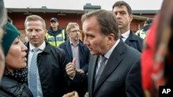 Le Premier ministre suédois Stefan Löfven rassurant des parents près d'une école où un homme a poignardé quatre personnes à Trollhattan, en Suède, le 22 octobre 2015.