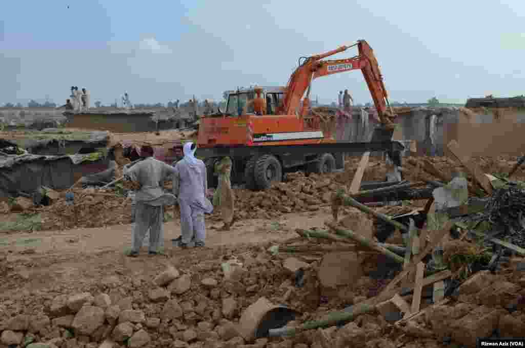 غیر قانونی مکانات مسمار کرنے کے بعد زمین کی سطح ہموار کرنے کے لیے بھاری مشینری کی مدد لی جا رہی ہے۔