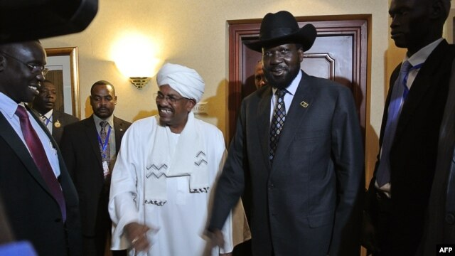 Sudanese President Omar al-Bashir (Center L) smiles after shaking hands with his South Sudanese counterpart Salva Kiir (Center R) following a meeting in the Ethiopian capital Addis Ababa, July 14, 2012.