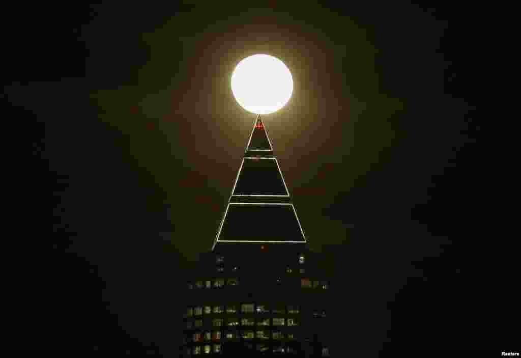 គេមើលឃើញព្រះច័ន្ទនៅជាប់នឹងអគារ Messeturm នៅក្នុងក្រុង Frankfurt ប្រទេសអាល្លឺម៉ង់ កាលពីថ្ងៃទី២៥ ខែមករា ឆ្នាំ២០១៦។