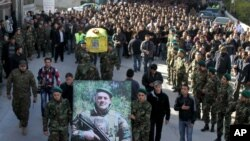 Hezbollah fighters, center, carry the coffin of their commander Ali Bazzi who was killed in Syria,Dec. 9, 2013. (AP Photo/Mohammed Zaatari)