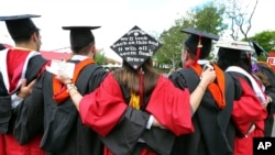 FILE - In this May 15, 2016, photo, students embrace as they arrive for the Rutgers graduation ceremonies in Piscataway, N.J. More Americans are getting buried by student debt, causing delays in home ownership, limiting how much people can save and leavi