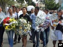 Amigos de Cesária com flores durante o cortejo fúnebre