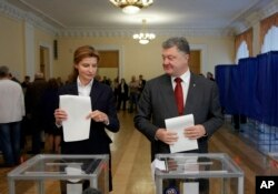 Ukrainian President Petro Poroshenko, right, and his wife, Maria, right, cast their ballots at a polling station during local election in Ukraine, Oct. 25, 2015.