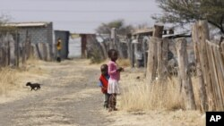 Children walk smong miner's shacks near Rustenburg, South Africa, Aug. 28, 2012.