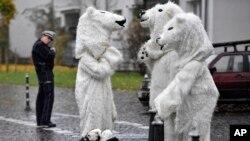 Manifestantes disfrazados de osos polares conversan luego de una protesta bajo la mirada de un policía en una calle cercana a la Conferencia COP 23 Fiji de la ONU para el Cambio Climático, en Bonn, Alemania. Nov. 11, 2017.