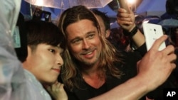 """U.S. actor Brad Pitt poses for a photo with a fan upon arrival at the South Korea premiere of his latest film """"World War Z"""" in Seoul on June 11, 2013."""