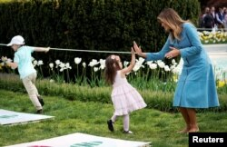 U.S. first lady Melania Trump high fives a child at the hopscotch station during the 2019 White House Easter Egg Roll on the South Lawn of the White House in Washington, April 22, 2019.