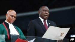 ប្រធានាធិបតីជាប់ឆ្នោតអាហ្វ្រិកខាងត្បូងលោក Cyril Ramaphosa (ស្ដាំ) ស្បថចូលកាន់តំណែងនៅក្បែរប្រធានផ្នែកយុត្តិធម៌ លោក Mogoeng Mogoeng នៅកីឡដ្ឋាន Loftus Versfeld ក្នុងរដ្ឋធានីប្រេតូរីយ៉ា ប្រទេសអាហ្វ្រិកខាងត្បូង កាលពីថ្ងៃទី២៥ ឧសភា ២០១៩។