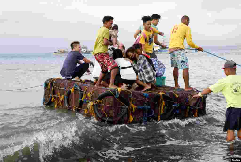 Stranded passengers ride on a makeshift raft after all ferry service were cancelled, a day after a Philippine vessel capsized because of bad weather in Infanta, Quezon in the Philippines.