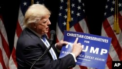 """Campaign 2016 Trump: Republican presidential candidate Donald Trump holds up a """"Christian Conservatives for Trump"""" sign at a rally, Wednesday, Sept. 28, 2016, in Council Bluffs, Iowa."""