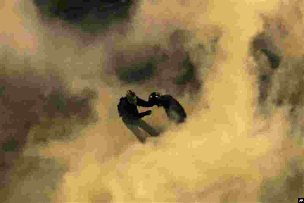 Protesters are seen through smoke from a tear gas canister throw by riot police outside the Embassy of the United States, right, in Athens, on Thursday, Nov. 17, 2011. Masked youths clashed with riot police outside Greece's parliament and the U.S. embass