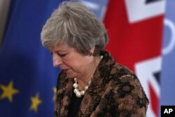 FILE - British Prime Minister Theresa May walks by the Union flag and the EU flag as she departs a media conference at an EU summit in Brussels, Dec. 14, 2018.