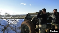 A Free Syrian Army fighter uses binoculars near the Menagh military airport, in Aleppo's countryside, Syria, January 10, 2013.