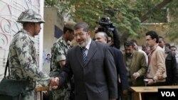 Jurubicara Ikhwanul Muslimin, Mohammed Morsi menyalami seorang tentara Mesir sebelum pemilu parlemen di Kairo (28/11). Ikhwanul Muslimin unggul dalam perolehan kursi parlemen dari hasil sementara pemilu.