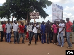 """Protesters gather along the road where the ECOWAS delegation traveled in Ouagadougou, Burkina Faso, Sept. 24, 2015. The sign's message in French """"No amnesty for Diendéré."""" (VOA / E. Iob)"""