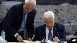 Presiden Palestina Mahmoud Abbas (kanan) menandatangani proposal untuk pengakuan dari PBB di Tepi Barat (1/4), meskipun sebelumnya telah berjanji untuk menangguhkan hal itu dalam 9 bulan negosiasi dengan Israel. Pengajuan ini dilakukan setelah Israel tidak membebaskan tawanan Palestina seperti disepakti sebelumnya.
