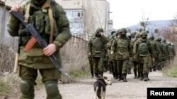 Para pria bersenjata diyakini sebagai orang-orang Rusia berjalan di luar pangkalan militer Ukraina di Perevalnoye, dekat Krimea (14/3).