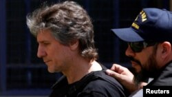 Former Argentine Vice President Amado Boudou is escorted by a member of Argentina's Coastguards as he arrives to a Federal Justice building in Buenos Aires, Argentina, Nov. 3, 2017.
